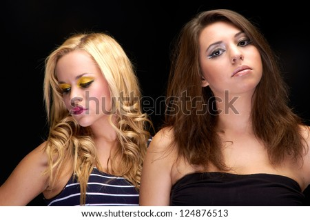 Closeup photo of two young girls in the studio against dark background