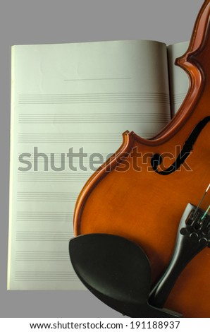 Closeup photo of violin on note sheet background isolated on gray background