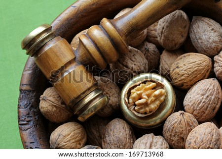 Closeup photo of Walnuts in a vintage wooden nut bowl with a Nutcracker hammer, Mallet with brass head easy to crack hard shell
