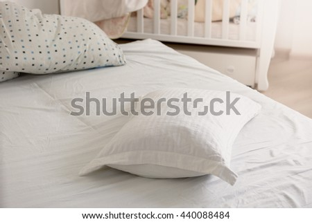 Closeup photo of white pillow on untidy bed at sunny day