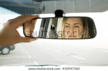 Closeup photo of woman adjusting car mirror and looking in the reflection - stock photo
