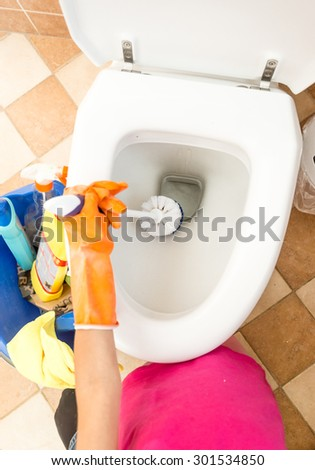 Closeup photo of woman in rubber gloves cleaning toilet with brush