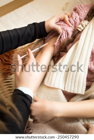 Closeup photo of woman making injection to little girl lying in bed - stock photo