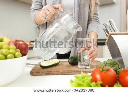 Closeup photo of woman pouring water in glass on kitchen - stock photo