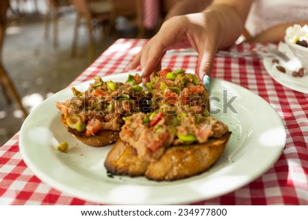 Closeup photo of woman taking bruschetta with tuna from plate at restaurant - stock photo