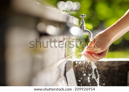 Closeup photo of woman washing hands in a city fountain  - stock photo