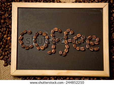 "Closeup photo of word ""coffee"" written by coffee beans on black chalk board - stock photo"