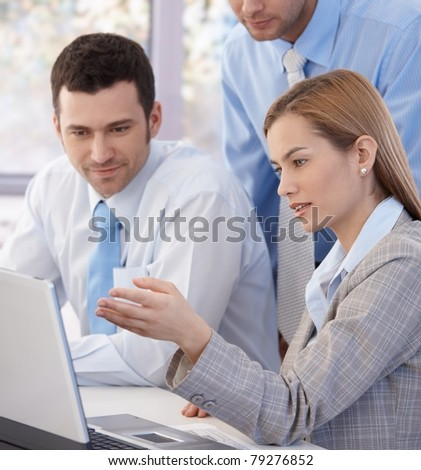 Closeup photo of young colleagues working together in bright office, looking at screen.? - stock photo