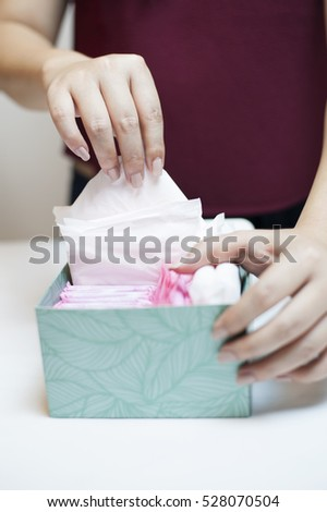 Closeup photo of young woman picking sanitary napkin out of green box