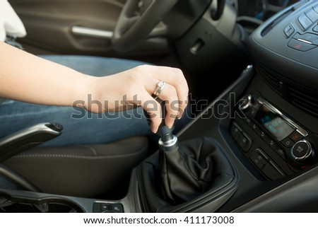 Closeup photo of young woman shifting gearbox in car