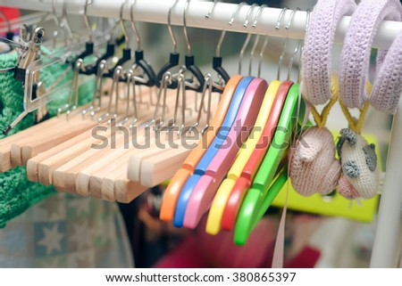 Closeup photo on colorful hangers hanging on rack
