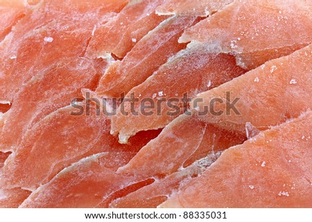 Closeup photo texture of frozen sliced raw salmon fish.