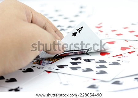 Closeup photos that focuses on the ace card of spade in the hand,on the background from the stack of cards. - stock photo