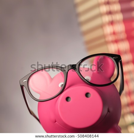 closeup picture of a piggy bank wearing glasses in front of a pile of books with copyspce, studio picture