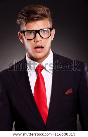 closeup picture of a young business man acting surprised with his mouth opened, against dark background