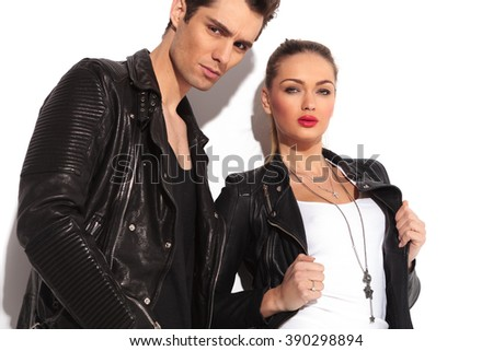 closeup picture of a young fashion couple in leather jackets, woman holding her collar and man standing next to her in studio - stock photo