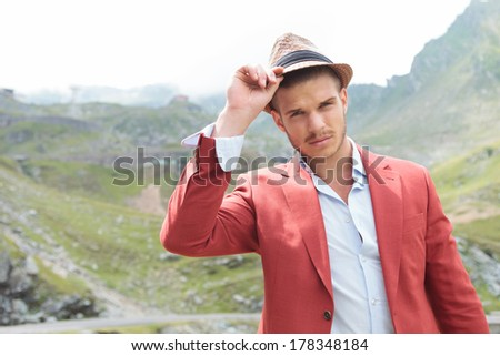 closeup picture of a young fashion man posing outdoor with his hand on his hat while looking into the camera - stock photo