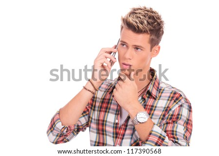 closeup picture of an attractive young man posing pensive on the phone - stock photo