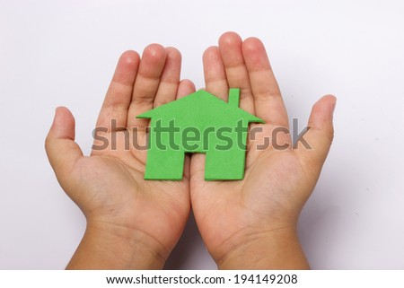 closeup picture of child hands holding green house - stock photo