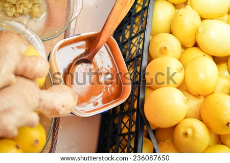 closeup picture of food making process wooden spoon in bowl & organic healthy ingredients as lemon, honey & ginger - stock photo