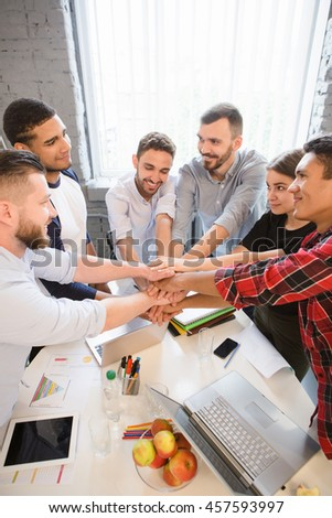 Closeup picture of happy business people showing teamwork in office. Cheerful executives standing round table and looking at each other.