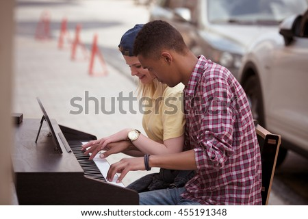 Closeup picture of man and woman playing piano outdoors all together. People playing and singing songs. Keyboard of piano concept. - stock photo