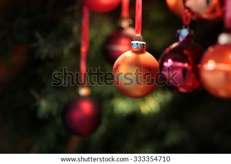Closeup picture of orange festive bauble hanging on Christmas tree among other shiny decorations with blurred background - stock photo
