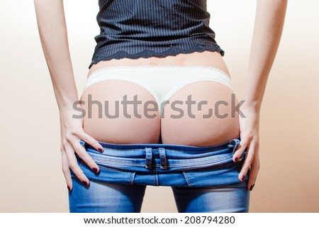 closeup picture of sensual hot buttocks in white lace underwear. slim fitness young woman standing in jeans having fun posing showing her excellent shape bum on light copy space background - stock photo