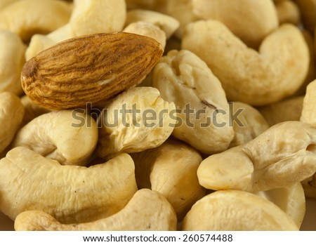Closeup picture of standing out almond nut among cashew nuts symbolizing individuality concept, difference and choice - stock photo