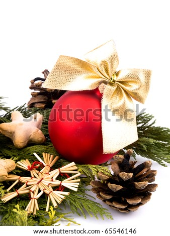 Closeup picture of thuja branches, red glass ball, spices and small wooden figure on white background.