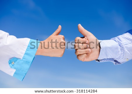 Closeup picture of thumbs up between doctors over blue sky sunny outdoors background - stock photo