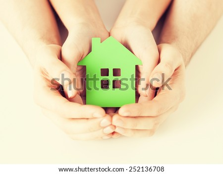 closeup picture of woman and man hands holding green house - stock photo