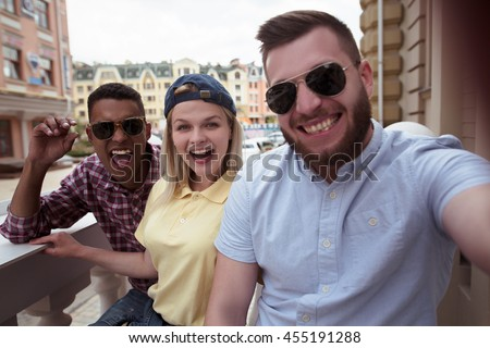 Closeup picture of young people smiling for camera. Happy friends in sunglasses making selfie on mobile or smart phone outdoor.