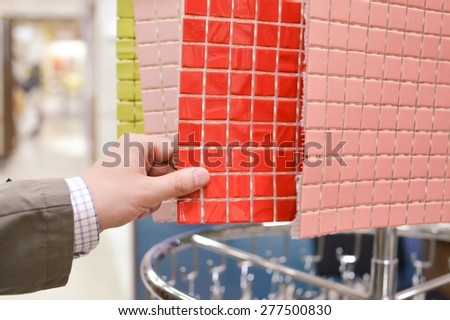Closeup picture on hands choosing or presenting colorful samples - stock photo