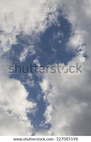 Closeup picturesque photo of many white and grey fluffy clouds on dark blue sky background, vertical picture - stock photo