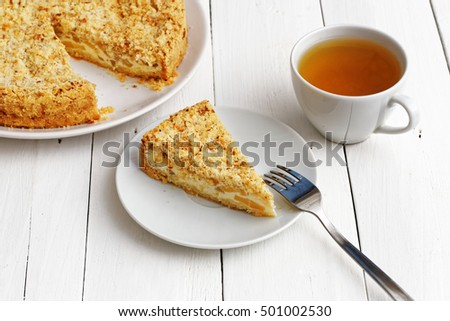 Closeup piece of homemade pie with cheese and apples, cup of tea and fork on white wooden table. Shallow focus.
