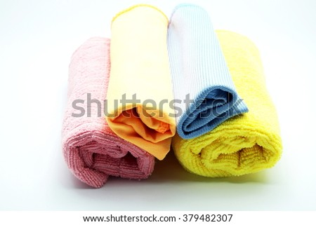 Closeup pile of colorful microfiber towel/cloth for car wipe with roll pattern on gray-white background. Focus on head rolls.