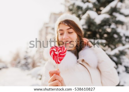 Closeup pink heart lollipop in hands winter girl background chilling on street full with snow in sunny morning. White knitted hat, enjoying. Delicious, sweet life, winter holidays
