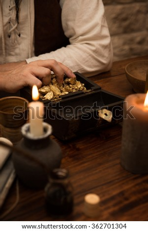 Closeup, Pirate with a treasure of gold, medieval table with candles, quill and a mug - stock photo