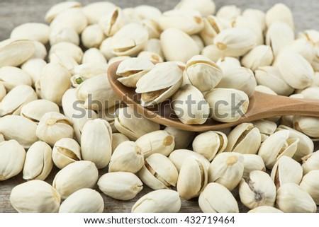 Closeup pistachios in a wooden spoon.Selective focus. - stock photo