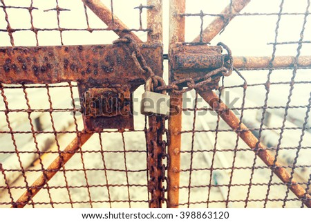 Closeup portable lock on chain on unpainted rusty metal gate doors outdoor on blurred background - stock photo