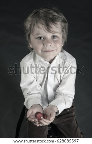 closeup portrait a beautiful little boy holding red heart in hands on a gray background studio