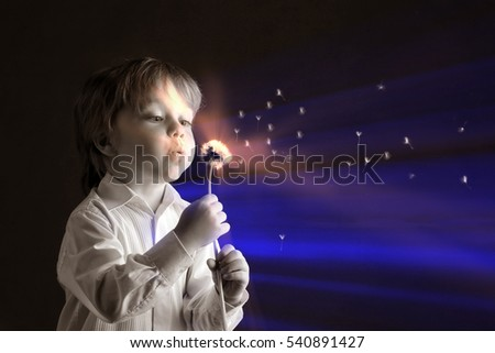 closeup portrait adorable boy with dandelion on a dark background studio