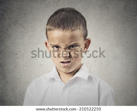 Closeup portrait Angry, displeased child Boy looking at you camera, mad about something, isolated grey wall background. Negative human emotions, feelings, facial expression, perception, body language - stock photo