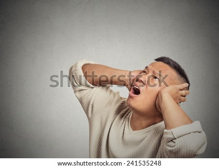 Closeup portrait angry mad unhappy stressed man covering his ears looking up, stop making loud noise it's giving me headache isolated grey wall background. Negative human  emotion, face expression - stock photo