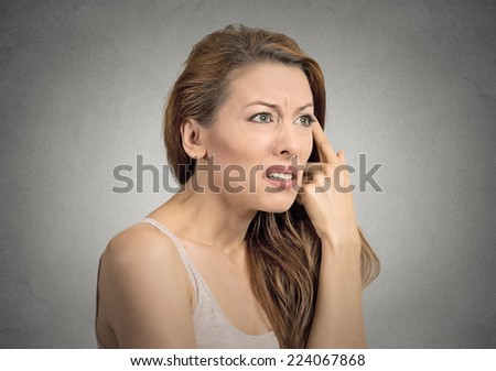 Closeup portrait angry mad young woman gesturing with her finger against temple asking are you crazy isolated grey wall background. Negative human emotion facial expression feeling body language - stock photo