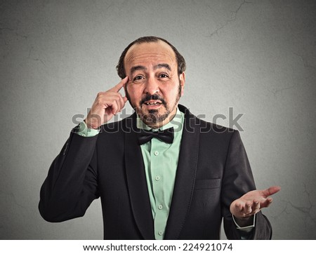 Closeup portrait angry middle aged business man gesturing with his finger against his temple, asking are you crazy? isolated grey wall background. Negative human emotion face expression body language - stock photo