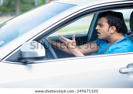 Closeup portrait, angry young sitting man pissed off by drivers in front of him and gesturing with hands, isolated city street background. Road rage traffic jam concept. - stock photo