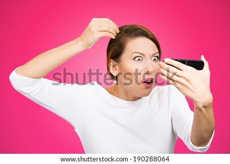 Closeup portrait, annoyed woman looking worried at white color hair or balding, isolated pink background. Negative human emotion facial expression feelings, attitudes, reaction, situation - stock photo