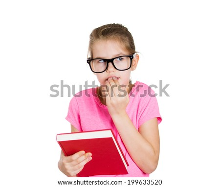 Closeup portrait anxious little girl with glasses, holding book, biting fingernails, back to school concept, isolated white background in studio. Human emotion, facial expression, reaction, perception - stock photo